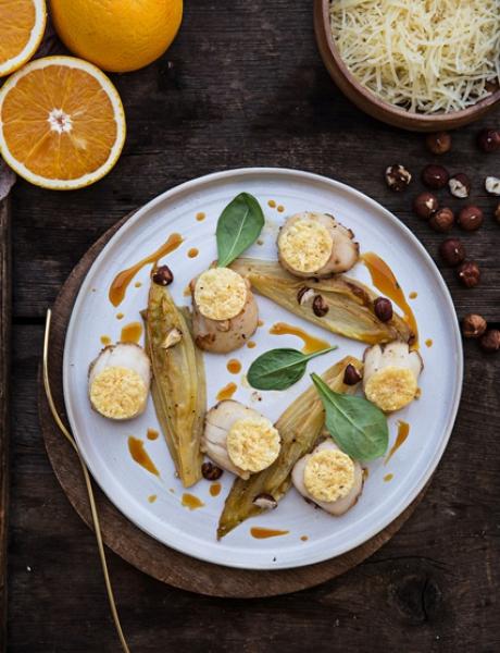 Vieiras con chips de gruyère, endivias y zumo de naranja