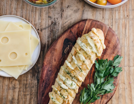 Pan de ajo con mantequilla de perejil y lonchas de queso emmental Entremont