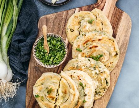 Panes hechos a la sartén con cebolletas y porción de queso emmental Entremont